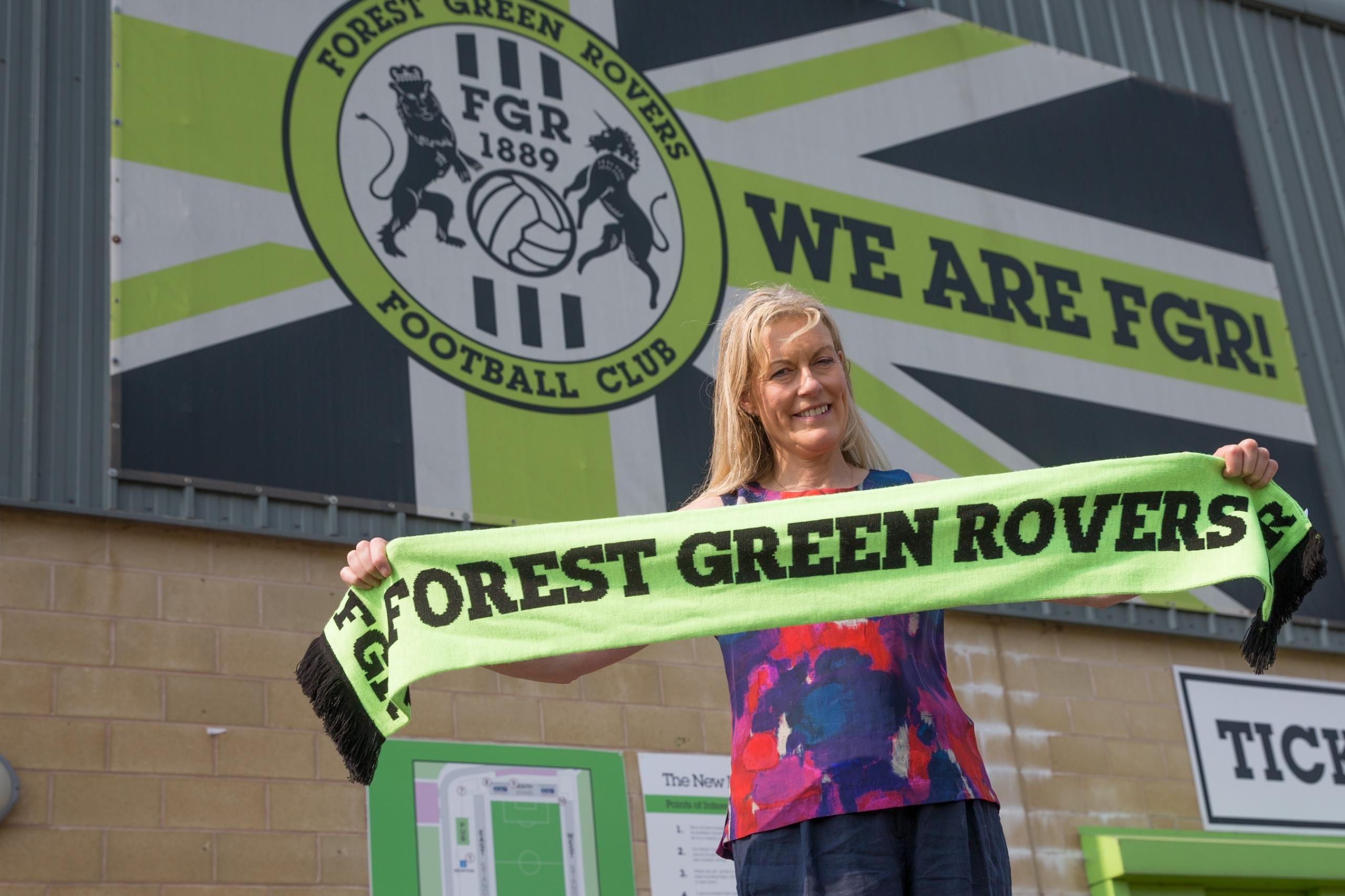 Helen holding FGR scarf outside the stadium, big FGR flag in teh background